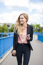 Smiling businesswoman walking on a bridge holding smartphone - DIGF000772