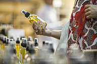 Close-up of woman holding scent bottle in shop - ZEF009092
