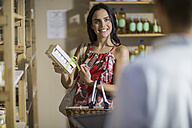 Woman holding product in health shop - ZEF009095