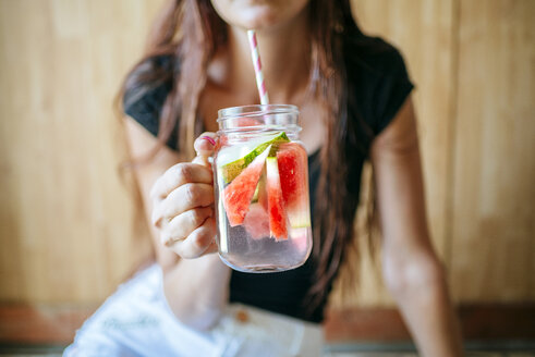 Close-up of woman holding a glass of watermelon - KIJF000597