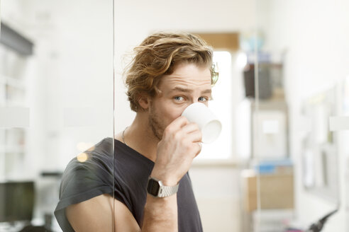 Young man drinking coffee in office - PESF000207
