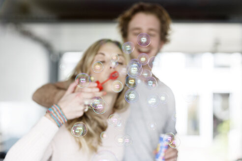 Young couple blowing soap bubbles - PESF000213