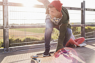 Young man riding skateboard on parking level - UUF008107