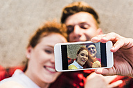 Selfie of young couple lying down - UUF008116