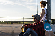 Young couple with skateboard and beer bottle enjoying the sunset - UUF008125