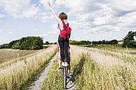 Young woman standing on bicycle rack - UUF008149