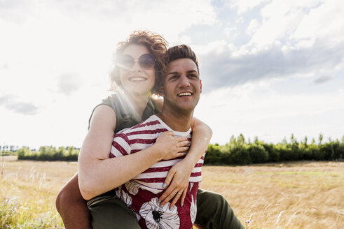Happy young man carrying girlfriend piggyback in the nature - UUF008155
