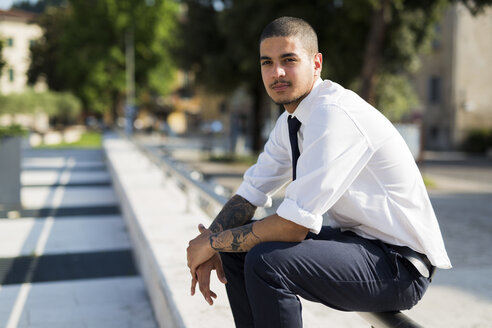 Portrait of young businessman with tatoos on his forearms sitting on railing - GIOF001252