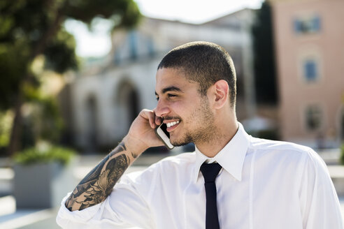Smiling young businessman telephoning with smartphone - GIOF001255