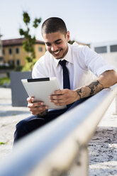 Smiling young businessman with tablet - GIOF001258