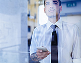 Young businessman behind glass pane - GIOF001264
