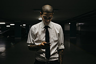 Young businessman standing in a gloomy car park looking at cell phone - GIOF001267