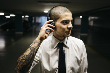 Young businessman with tattoo on his forearm with headphones in a gloomy car park - GIOF001270