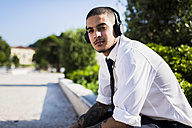 Young businessman with headphones sitting on a wall at sunlight - GIOF001273