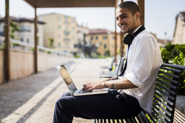 Smiling young businessman sitting on a bench using laptop - GIOF001276