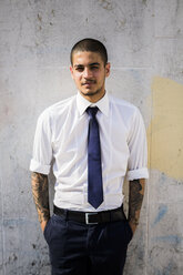 Portrait of young businessman with tattoos on his forearms - GIOF001285