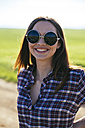 Portrait of smiling young woman wearing oversized sunglasses - DERF000032