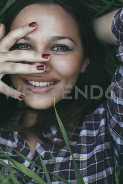 Portrait of smiling young woman  lying in a field - DERF000035