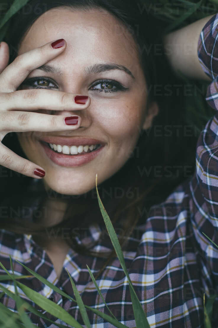 Portrait of smiling young woman  lying in a field - DERF000035 - MelkinImages/Westend61