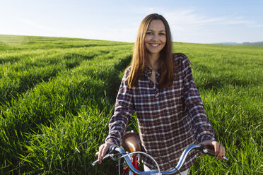 Portrait of smiling young woman with bicycle standing in wheat field - DERF000038