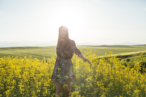 Young woman standing in a rape field at backlight - DERF000041