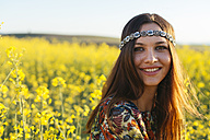 Portrait of smiling young hippie in a rape field - DERF000044