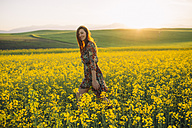 Smiling young woman walking in a rape field at twilight - DERF000047