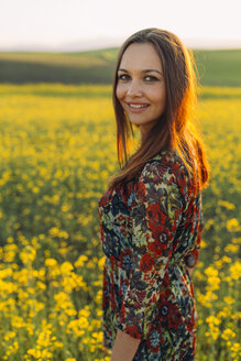 Portrait of smiling young woman standing in a rape field - DERF000050