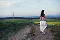 Back view of young woman walking on a dirt track - DERF000053