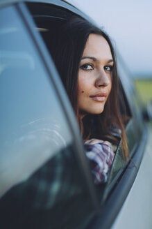 Portrait of young woman peeking from car window - DERF000056