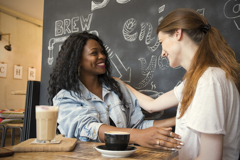 Two friends meeting in cafe, embracing - ONF000946