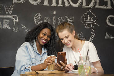 Two friends in cafe looking at smart phone - ONF001000