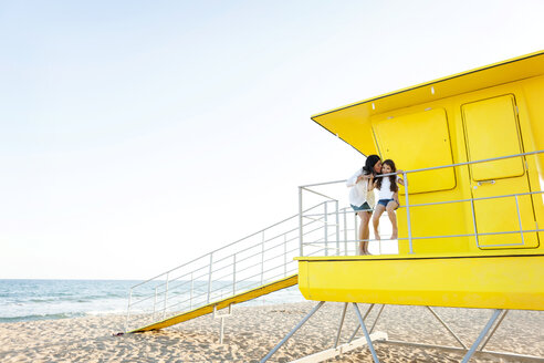 Mother kissing her little daughter  on a yellow lifeguard stand - VABF000699