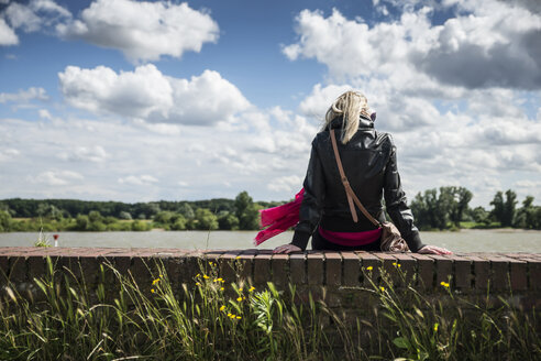 Woman sitting on wall, Rhine riverside - CHPF000231