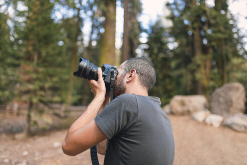 Young tourist man photographing in forest - EPF000114