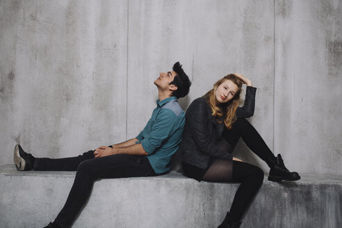 Young couple sitting in front of concrete wall - GCF000211