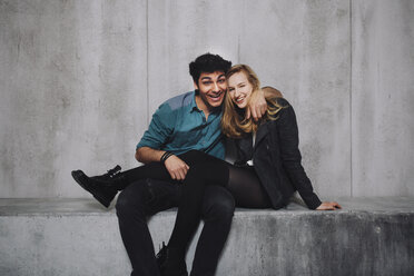Young couple sitting in front of concrete wall, laughing - GCF000214