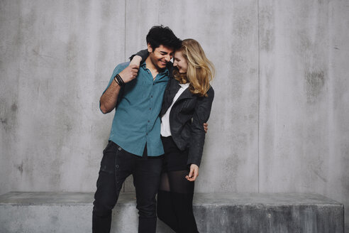 Young couple embracing in front of concrete wall - GCF000217