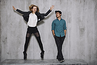 Couple in front of concrete wall, woman jumping - GCF000220