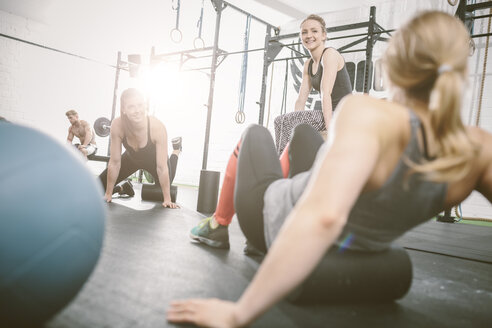 People in gym using foam roller - MAD000984