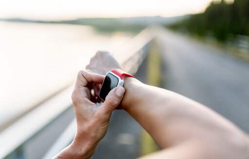 Woman adjustung settings of smart watch for outdoor training - MGOF002041
