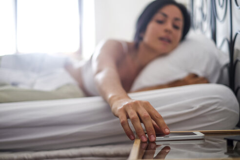 Young woman in bed, taking smartphone - SIPF000675