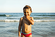 Happy little boy standing in front of the sea - VABF000705