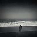 France, Contis-Plage, man on the beach during storm, monochrome - DWIF000762