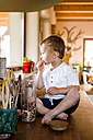Little boy is playing in kitchen, nibbling food - HAPF000615