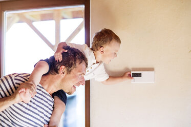 Father carrying son on shoulders, adjusting thermostat - HAPF000633