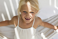 Portrait of smiling little girl with tooth gap in a hammock - TCF005010