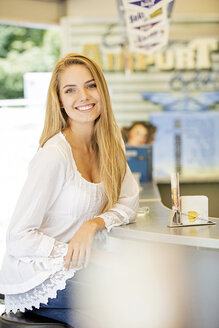 Young woman sitting at counter of a food stand - GD001063