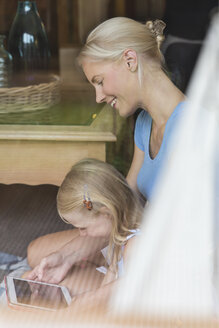 Mother and little daughter sitting behind window pane looking together at tablet - MIDF000762