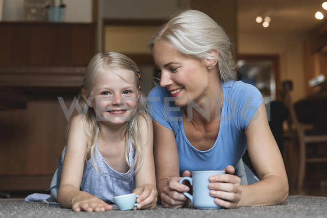 Mother and little daughter lying side by side on the floor holding cups - MIDF000765 - Miriam Dörr/Westend61